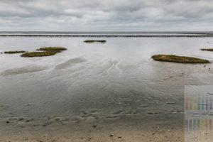 Tief hängende graue Wolken über dem Wattenmeer bei Ebbe vor Keitum auf der Insel Sylt