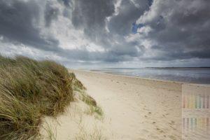 Bedrohlich wirkende Regenwolken formieren sich über dem Strand des Königshafens, einer Bucht am Sylter Ellenbogen.Es weht ein kräftiger Westwind. Im Hintergrund die Ortschaft List