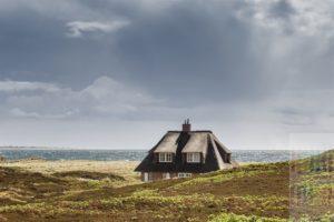 Reetdachhaus steht in den Dünen von Hörnum im Süden der Insel Sylt. Am Horizont ist die Küstenlinie der Nachbarinsel AMrum zu sehen