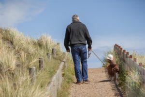 Mann führt seinen Hund (Border Collie) wie vorgeschrieben durch die Sylter Dünenlandschaft