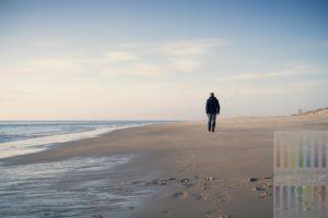 Mann (Rückansicht) spaziert allein am Sylter Nordseestrand Richtung Westerland.