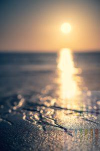 Ablaufend Wasser am Sylter Strand tief stehender Sonne über der Nordsee, Offenblende